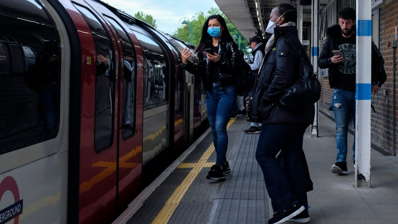Commuters, some wearing protective masks to protect against coronavirus stand on the platform at Leytonstone underground station, in London, Monday, May 18, 2020. (AP Photo/Alberto Pezzali)