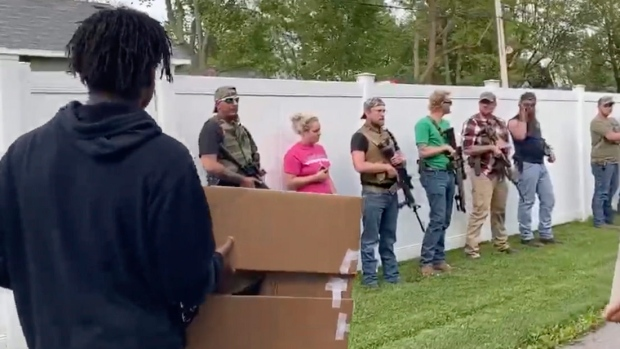 21 residents armed with guns stand at sidelines of peaceful protest