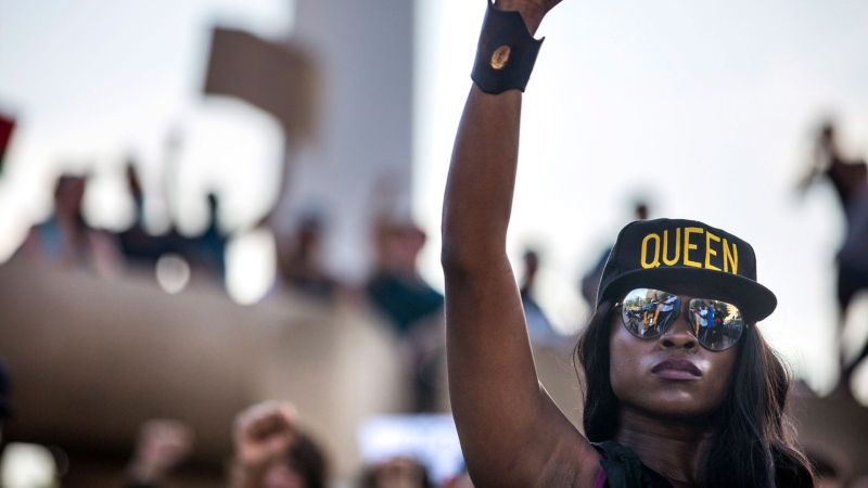Jennifer Akabue raises her fist with other protesters as they participate in an 8-minute and 46-second kneel in honor of George Floyd during a demonstration at Dallas City Hall to denounce police brutality and systemic racism, in Dallas, on Thursday, June 4, 2020. (Lynda M. Gonzalez/The Dallas Morning News via AP)