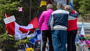A family pays their respects to victims of the mass killings at a checkpoint on Portapique Road in Portapique, N.S. on Friday, April 24, 2020. THE CANADIAN PRESS/Andrew Vaughan