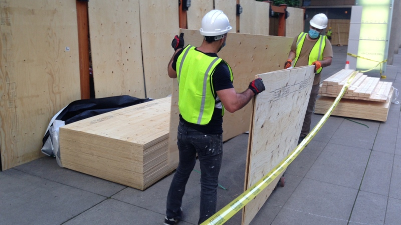 Crews are seen putting up plywood sheets outside College Park on Friday morning. (Cam Woolley)