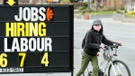 A woman checks out a jobs advertisement sign during the COVID-19 pandemic in Toronto on Wednesday, April 29, 2020. THE CANADIAN PRESS/Nathan Denette
