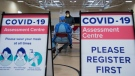 Muhammad Junayed, centre back, gets instructions for being tested for COVID-19 from a health care worker at a pop-up testing centre at the Islamic Institute of Toronto during the COVID-19 pandemic in Scarborough, Ont., on Friday, May 29, 2020. THE CANADIAN PRESS/Nathan Denette