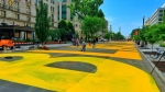 Giant, yellow letters are painted on a busy Washington D.C. street spelling out  'BLACK LIVES MATTER.' (Chris Turner/CNN)