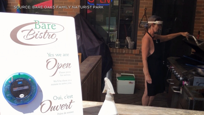 A woman cooks at a barbeque at the Bare Bistro at a naturist resort near Newmarket, Ont. (Courtesy: Bare Oaks Family Naturist Park)