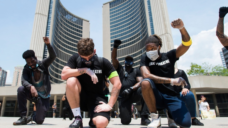 Protesters raise their fists at an anti-racism demonstration reflecting anger at the police killings of black people, in Toronto on Friday, June 5, 2020. THE CANADIAN PRESS/Nathan Denette
