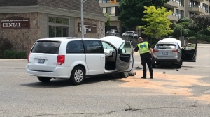 An unmarked Waterloo Regional Police (white van) and an SUV have been involved in a crash at a Kitchener intersection. (Dave Pettitt/CTV Kitchener)