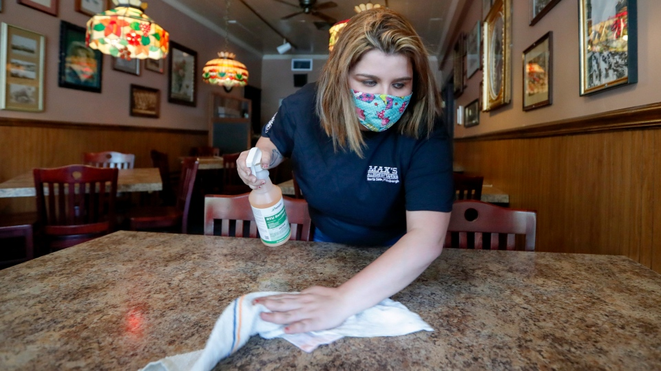 Sara Kennely, cleans one of the dining tables at Max's Allegheny Tavern, Thursday, June 4, 2020. (AP Photo/Keith Srakocic)