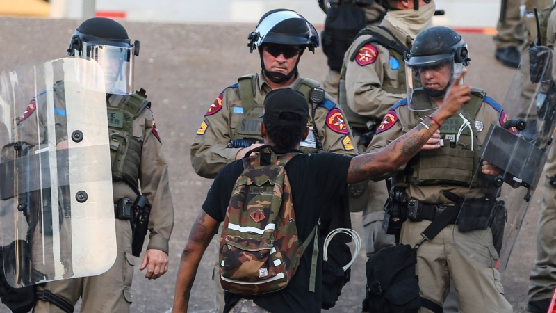 Texas State Police confront a protester as they protect the I-35 crossing near Austin Police Department HQ during a protest over the death of George Floyd, who died May 25 after being restrained by police in Minneapolis, in Austin on Thursday, June 4, 2020. (Lola Gomez / Austin American-Statesman via AP) / Austin American-Statesman via AP)