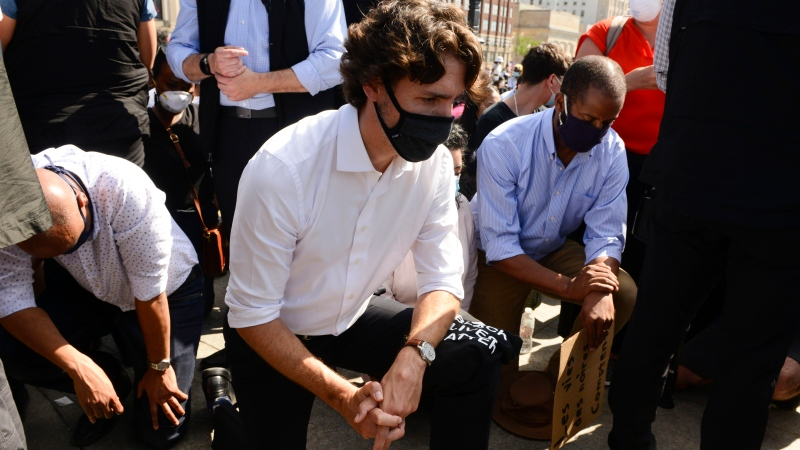 Prime Minister Justin Trudeau takes a knee during an 8 minute and 46 second silence as he takes part in an anti-racism protest on Parliament Hill during the COVID-19 pandemic in Ottawa on Friday, June 5, 2020. He is joined by Minister of Families, Children and Social Development Ahmed Hussen, left and Liberal MP Greg Fergus, right. THE CANADIAN PRESS/Sean Kilpatrick