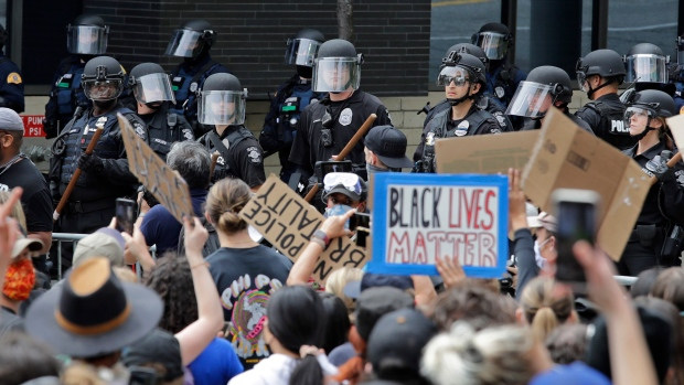 Police officers behind a barricade watch as protesters fill the street in front of Seattle City Hall on Wednesday, June 3, 2020, in Seattle, during protests over the death of George Floyd in Minneapolis. (AP Photo/Elaine Thompson)