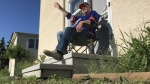 Rolland Sarasin waves from his front step. (Darcy Seaton/CTV News Edmonton)
