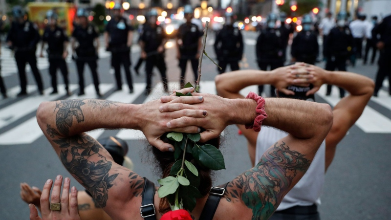 Protesters kneel in front of New York City Police Department officers before being arrested for violating curfew beside the iconic Plaza Hotel on 59th Street, Wednesday, June 3, 2020, in New York. Protests continued following the death of George Floyd, who died after being restrained by Minneapolis police officers on May 25. (AP / John Minchillo)