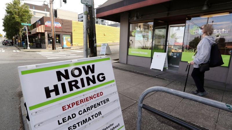 In this photo taken Thursday, June 4, 2020, a pedestrian wearing a mask walks past reader board advertising a job opening for a remodeling company, in Seattle. (AP / Elaine Thompson)