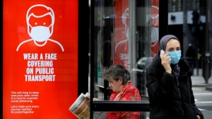 Passengers wait at a bus stop with a sign advising travellers to wear a face covering whilst travelling, in London, Friday, June 5, 2020. (AP Photo/Kirsty Wigglesworth)