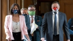 Wearing a Baseball-Quebec mask, Quebec junior Education Minister and minister responsible for the status of women Isabelle Charest, left, and Quebec Premier Francois Legault, right, walk to a news conference on the COVID-19 pandemic, Thursday, June 4, 2020 at the legislature in Quebec City. Charest announced the reopening of team sports in the coming week. Horacio Arruda, Quebec director of National Public Health, centre, walks behind. THE CANADIAN PRESS/Jacques Boissinot