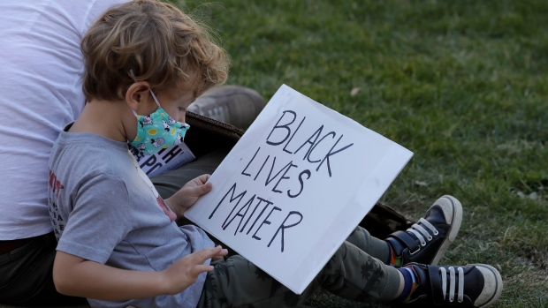 A child holds a Black Lives Matter sign in Oakland, Calif., Thursday, June 4, 2020, at a protest over the May 25 death of George Floyd, who died after being restrained by Minneapolis police. (AP Photo/Ben Margot)