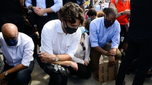 Prime Minister Justin Trudeau takes a knee during an 8 minute and 46 second silence as he takes part in an anti-racism protest on Parliament Hill during the COVID-19 pandemic in Ottawa on Friday, June 5, 2020. THE CANADIAN PRESS/Sean Kilpatrick