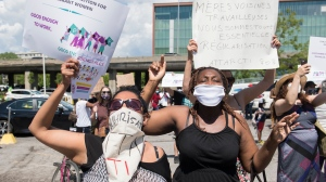 People hold up signs during a demonstration outside Prime Minister Justin Trudeau's constituency office in Montreal, Saturday, June 6, 2020, where they called on the government to give residency status to migrant workers as the COVID-19 pandemic continues in Canada and around the world. THE CANADIAN PRESS/Graham Hughes
