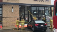 Fire crews helped extricate two people out of a vehicle Saturday after it crashed into a business.(Brandon Lynch/ CTV News Edmonton)