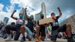 Anti-racism demonstrators take a knee in front of Toronto CIty Hall during a march on Saturday, June 6, 2020. THE CANADIAN PRESS/Frank Gunn