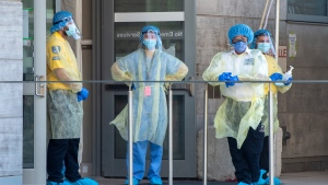 In this file photo, security guards and a heath-care worker wait for patients at the Women's College Hospital COVID-19 testing centre in Toronto on Saturday June 6, 2020. (THE CANADIAN PRESS / Frank Gunn)