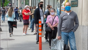 Masked customers line up outside a store in Montreal in this May 2020 file image. (THE CANADIAN PRESS / Ryan Remiorz)