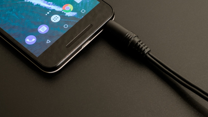 A cell phone connected to a charging cable is pictured. (Lum3n/Pexels)