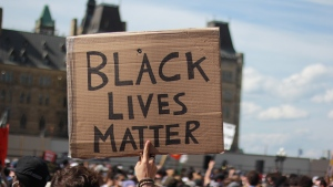 A protester in a crowd on Parliament Hill holds up a cardboard sign with the words 'Black Lives Matter'  during the 'No Justice Until Peace' march in Ottawa on June 5, 2020. (Skyler Walker/CTV Viewer)