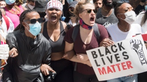 People attend a demonstration calling for justice for the death of George Floyd and all victims of police brutality, in Montreal, Sunday, June 7, 2020. THE CANADIAN PRESS/Graham Hughes