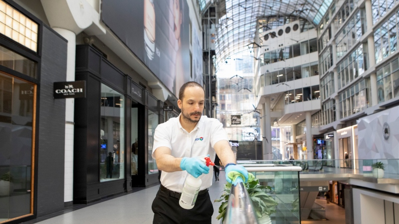 A cleaner wipes a glass panel at Toronto's Eaton Centre shopping mall on Saturday, March 21, 2020. Malls are beginning to re-open across the country as provinces cautiously ease physical distancing requirements, but mall operators are facing a much different environment than the one that preceded the arrival of the COVID-19 pandemic.THE CANADIAN PRESS/Chris Young