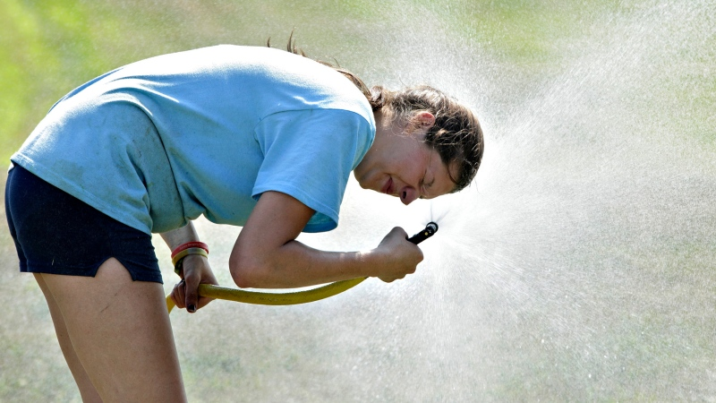 Becky Stap, of Stap Family Dairy Farm in Pine Bush, N.Y., sprays herself with a hose after using water from the hose to cool off a cow at the Orange County 4-H Showcase at Bergin Farm in Slate Hill, N.Y., on Thursday, July 18, 2013. Temperatures were in the mid-90s in the afternoon. (AP Photo/Times Herald-Record, Tom Bushey)