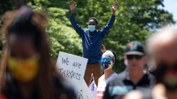 A man holds both arms up in the air as demonstrators protest, Sunday, June 7, 2020, near the White House in Washington, over the death of George Floyd, a black man who died after being restrained by Minneapolis police officers. (AP / Jacquelyn Martin)