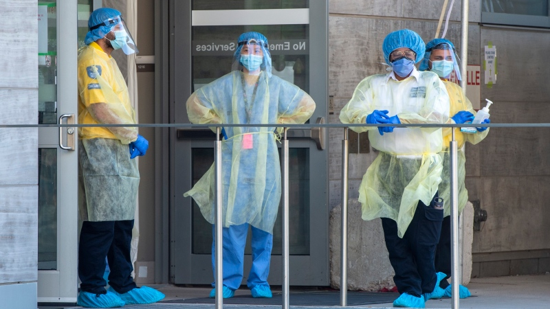 Security guards and a heath-care worker wait for patients at the Women's College Hospital Covid-19 testing centre on Saturday June 6, 2020. (THE CANADIAN PRESS/Frank Gunn)