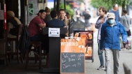 A man wears a protective face mask as he walks past a opened restaurant patio on Granville Street in Vancouver, Wednesday, May 20, 2020. British Columbia has entered into phase 2 of the provinces re-start plan allowing some business to reopen. (THE CANADIAN PRESS / Jonathan Hayward)