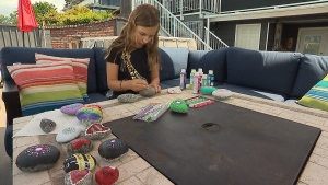 Teagan Ennis-Colliar, 8 years old, is hard at work painting rocks to scatter around her neighbourhood and bring joy.