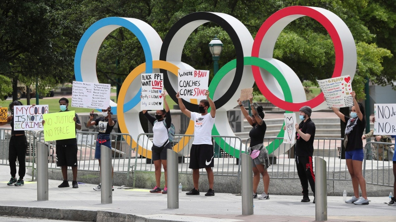 Protesters begin to form a line of solidarity around Olympic Park, Wednesday, June 3, 2020, in Atlanta, during a sixth day of protests over the death of George Floyd, a black man who was killed while in police custody in Minneapolis on May 25. (Curtis Compton/Atlanta Journal-Constitution via AP)