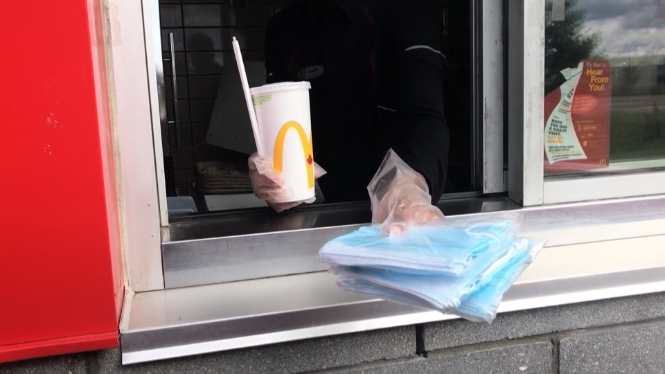 A McDonalds employee handing packages of masks out the drive-thru window during Alberta's first wave of mask distribution (file)