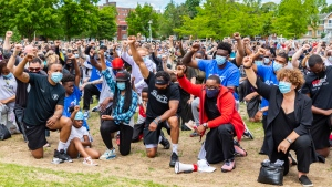 People take part in a silent kneeling protest at Loyola Park in NDG. (Photo: Eva Blue)
