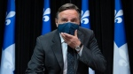 Quebec Premier Francois Legault holds his mask as he arrives at a news conference on the COVID-19 pandemic at the legislature in Quebec City. THE CANADIAN PRESS/Jacques Boissinot