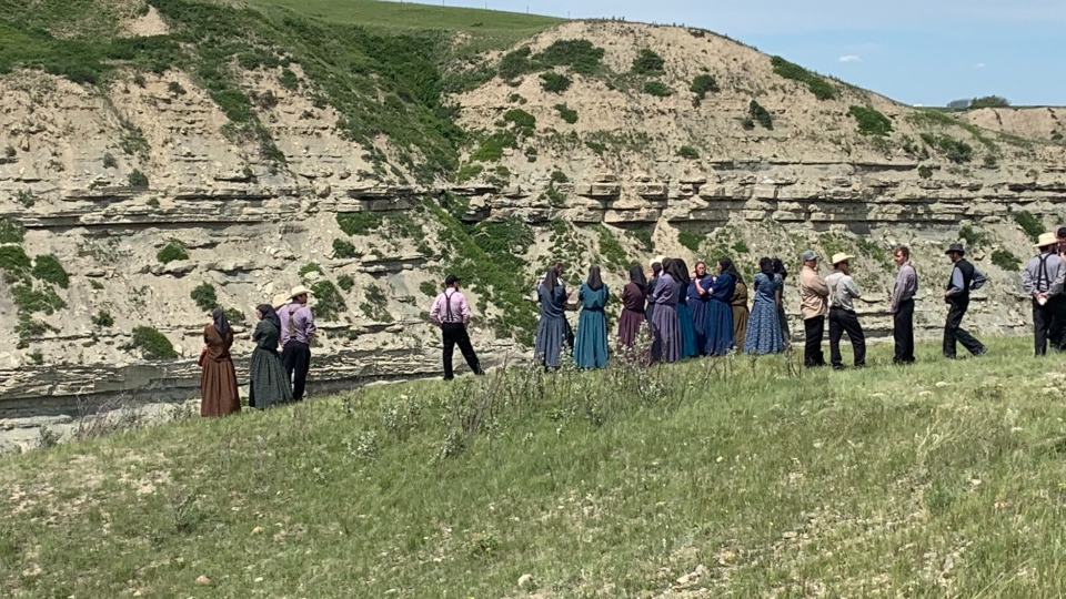 Members of the Spring Valley Hutterite Colony overlook an area where two teen girls drowned and a third was swept away in the St. Mary River in southern Alberta.