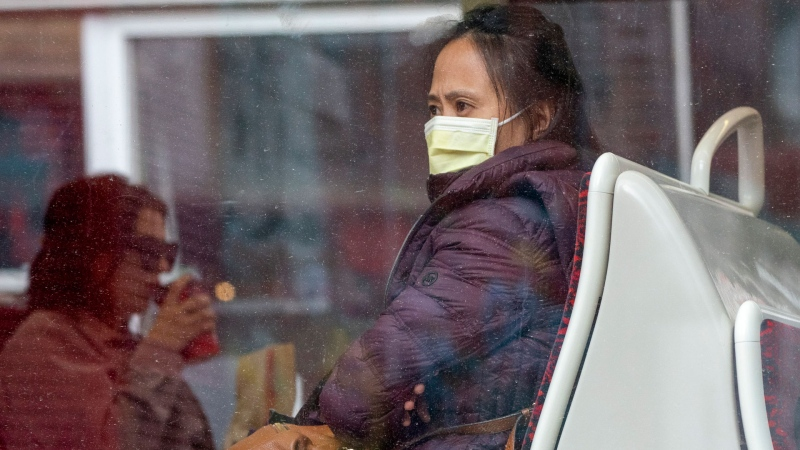 A woman wears a mask as she rides a TTC streetcar in Toronto on Friday, March 20, 2020. THE CANADIAN PRESS/Frank Gunn