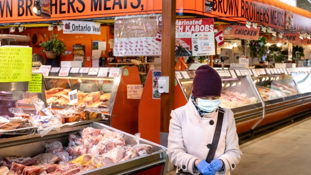 A shopper is seen in a quiet St. Lawrence Market in Toronto on Friday, March 20, 2020. The market normally has over 5,000 visitors on a typical Friday. THE CANADIAN PRESS/Chris Young