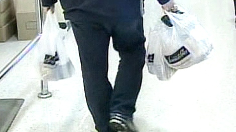 A shopper walks out of a grocery store holding platic shopping bags.