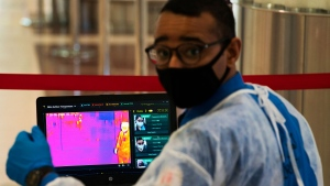 An official wearing a mask due to the coronavirus pandemic operates a temperature screening point at Dubai International Airport's Terminal 3 in Dubai, United Arab Emirates, Wednesday, June 10, 2020. The coronavirus pandemic has hit global aviation hard, particularly at Dubai International Airport, the world's busiest for international travel, due to restrictions on global movement over the virus. (AP / Jon Gambrell)