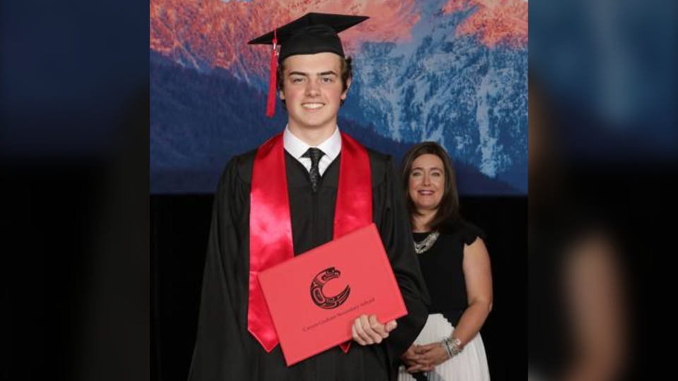 Carson Graham Secondary student Max Faber receives his high school diploma standing two metres away from Principal Suzette Dohm, a result of COVID-19 precautions that dramatically changed what graduation looked like for students in 2020.