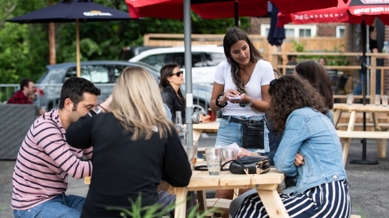 A server takes orders on the patio at Banditos, a restaurant in Ottawa, on its first day of reopening as Ontario moves into Stage 2 of its plan to lift lockdowns implemented in response to the COVID-19 pandemic, on Friday, June 12, 2020. THE CANADIAN PRESS/Justin Tang