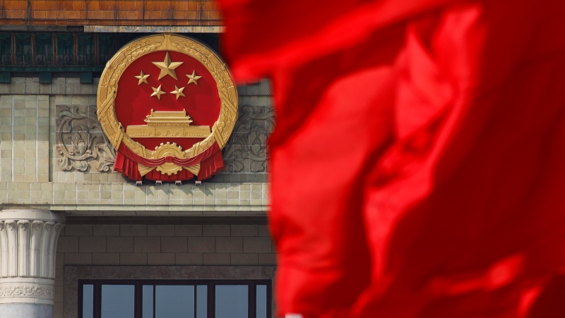 Red flags flutter in the wind near the Chinese national emblem outside the Great Hall of the People in this file photo taken Monday, March 4, 2019. (AP Photo/Andy Wong)