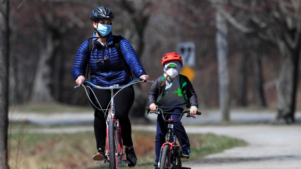 In this Wednesday, April 8, 2020, photo, bicyclists wear pandemic masks while riding in Portland, Maine. (AP Photo/Robert F. Bukaty)