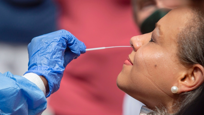 Dr. Janice Underwood gets a nasal-swab test by Danielle Edwards, of Chesapeake Regional Healthcare, for COVID-19 at Geneva Square in Chesapeake, Va., on Friday, June 5, 2020. (The' N. Pham/The Virginian-Pilot via AP)